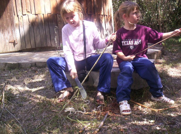Me and my younger sister in Kenya learning how to carve arrows out of sticks.