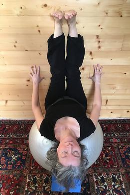 Catherine Bellières en étirement dorsal et en étirement des ischio-jambiers sur un gros ballon.