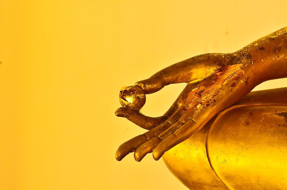 buddha statue hands on yellow background.jpg
