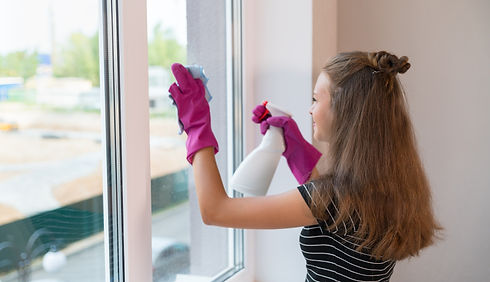 Young woman wearing rubber gloves cleani