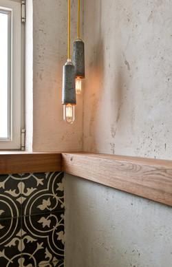 אריחי בטון מצוירים בגב קיר האסלה מתכתבים עם מנורות בטון של יואב וספי. שירותי האורחים..