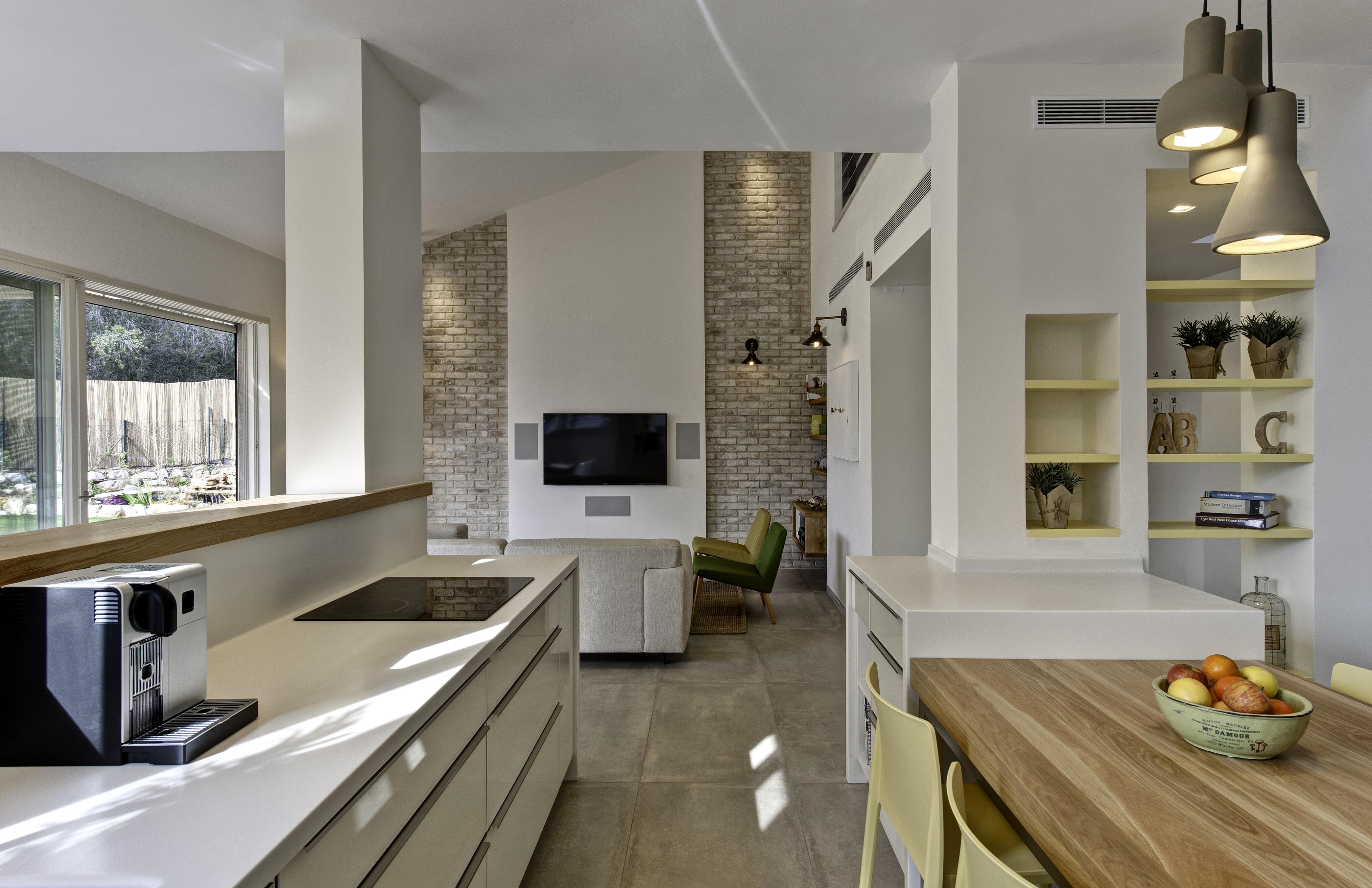 מבט מהמטבח אל הסלון. קירות אבן אורכיים מדגישים את גובה התקרה בסלון