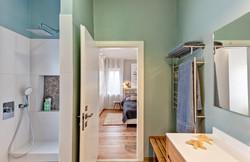מבט מחדר הרחצה לחדר השינה של ההורים. ספסל עץ ממשיך את ארון הכיור