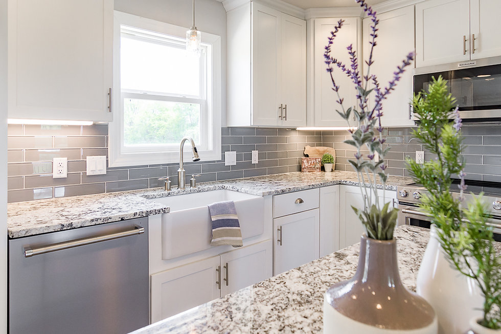 Bright Kitchen with Granite Counter Tops Stainless Steel Appliances and White Cabinetry