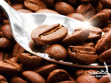 Coffee beans and spoon close up with sun