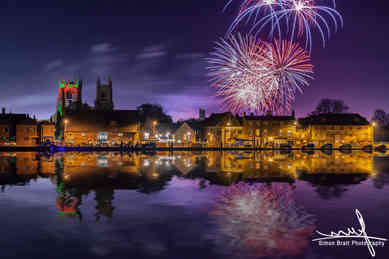 Firework display over town and river