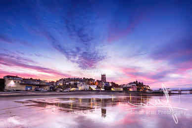 Pink sunset reflections over Cromer town at dusk