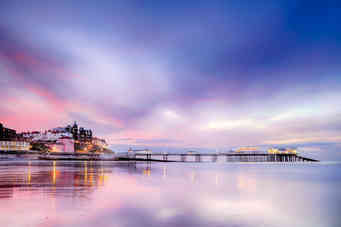 Famous Cromer pier in Norfolk England with pink sunset