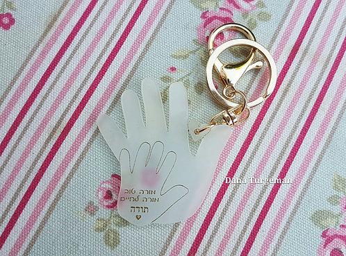 יד ביד לאורך כל הדרך.. מחזיק מפתחות מרגש יד קטנה וגדולה אוחזים בדרך המשותפת