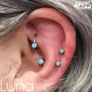 Fresh helix piercings with mint Swarovski Zirconia and healed conch with capri blue opal