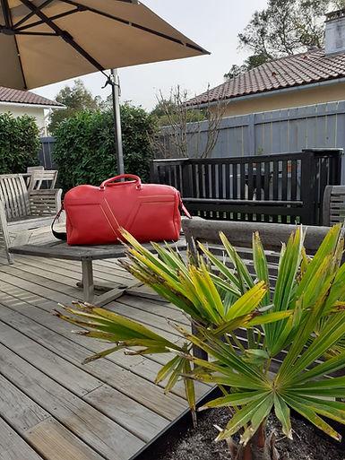 Sac de voyage cuir rouge terrasse.jpeg