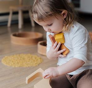 photo-of-child-holding-wooden-blocks-393