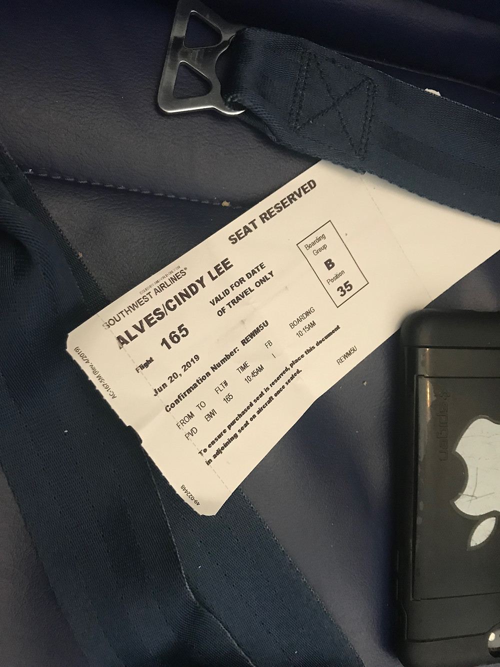 Photo of airplane seat with Seat Reserved ticket and a Black iPhone face down