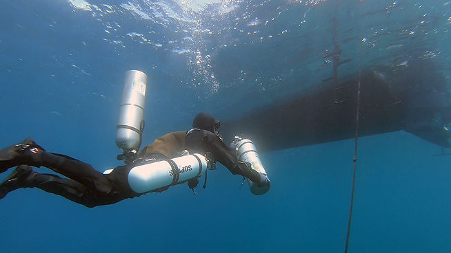 Technical sidemount diver making a boat exit