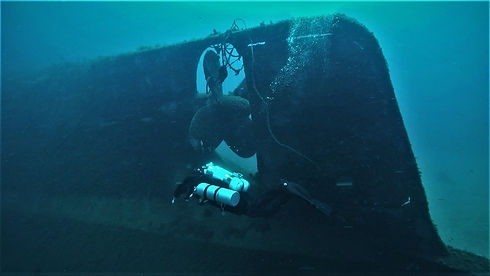 Technical diver passing the rudder of a ship wreck