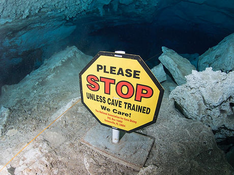Stop unless cave trained sign at a cave entrance