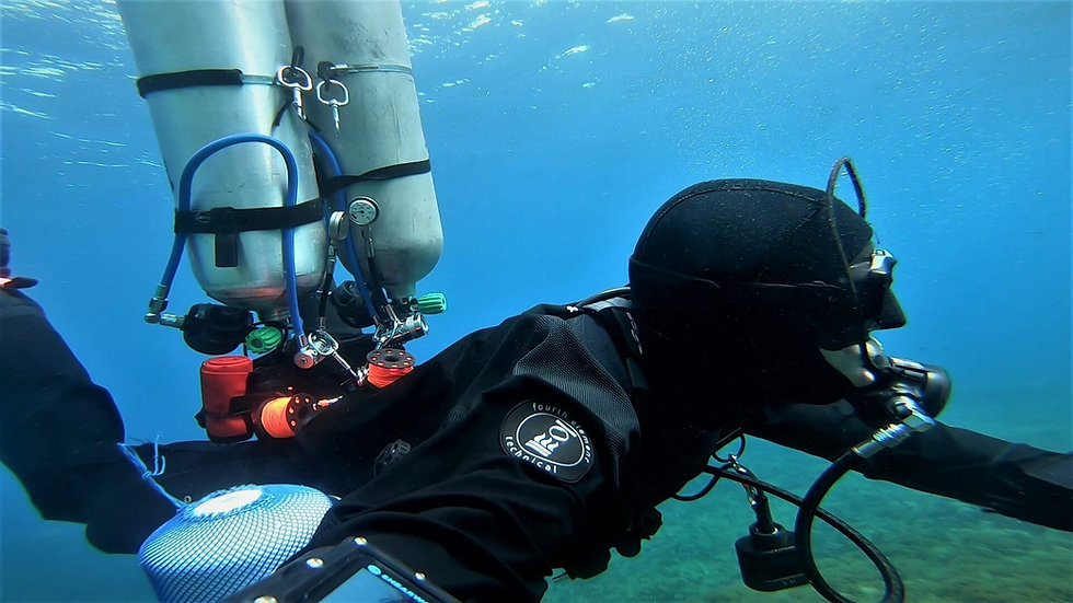 Sidemount Diver preparing to exit the water with empty stage cylinders