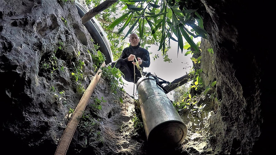 Cave diver lowering cylinders into a cave entrance