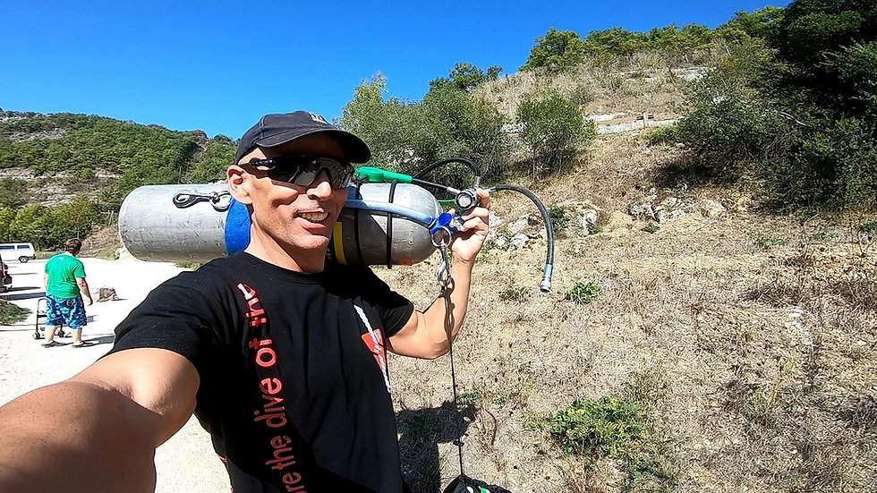 Cave Diver Carrying a stage cylinder to the cave entrance in France