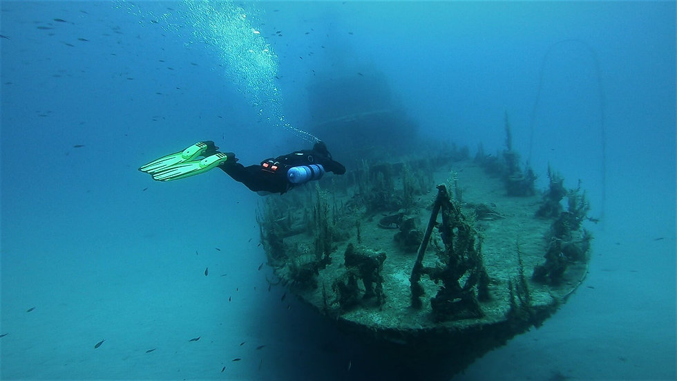 Sidemount Diver cruising over the outside of a wreck