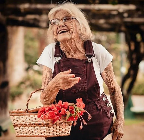 Happy elderly lady with flowers