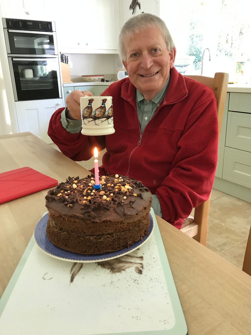 A man holds up a mug with pheasants on and smiles at the camera. Infront of him is a massive chocolate cake with happy birthday candles in