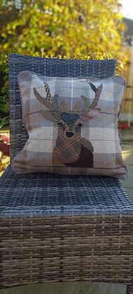 A one-off appliquéd stag cushion on a 100% wool tweed cushion with pipe