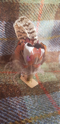 One-off feather brooch with natural feathers placed into a spent bullet