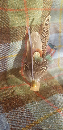 One-off feather brooch withnaturalfeathers placed into a 9mm spent bullet.