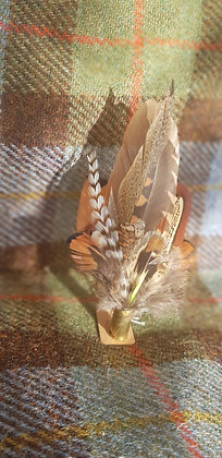 One-off feather brooch with natural feathers placed into a 9mm spent bullet.