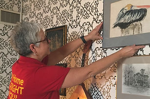 Goldilocks Solutions carefully hanging art in clients home