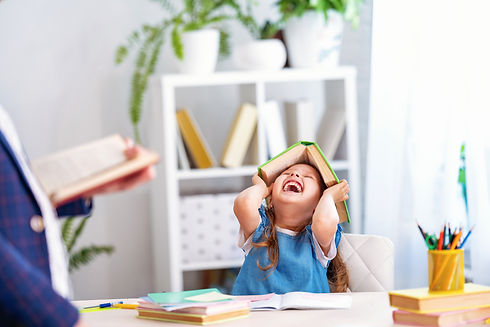 laughing child holding a book on her head in excitement