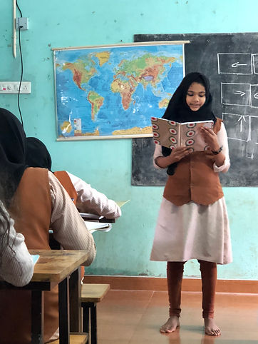 girl reading to classmates from a notebook