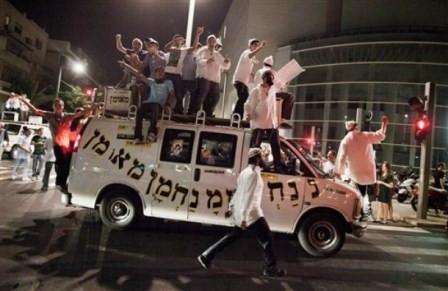 Ultra-Orthodox Jews of the Bratslav Hasidic sect dance on top of a van with the name of their spiritual leader Rabbi Nachman of Uman (AP Photo/Dan Balilty)