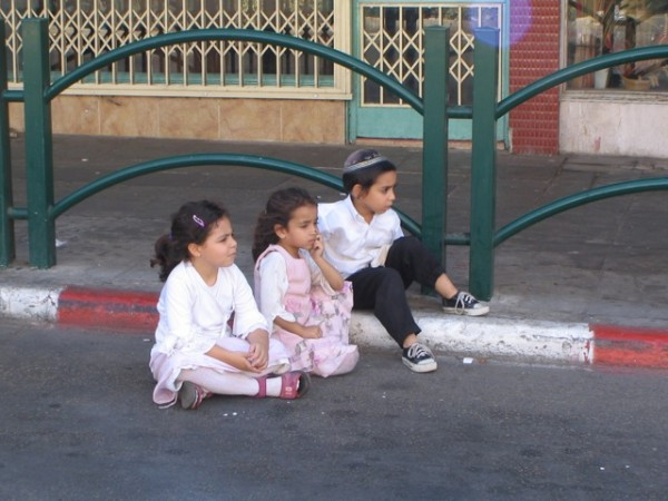 Orthodox children watch on as the secular kids bike.
