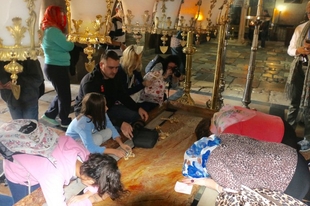 People seek favor at the Anointing Stone at the Church of the Holy Sepulchre