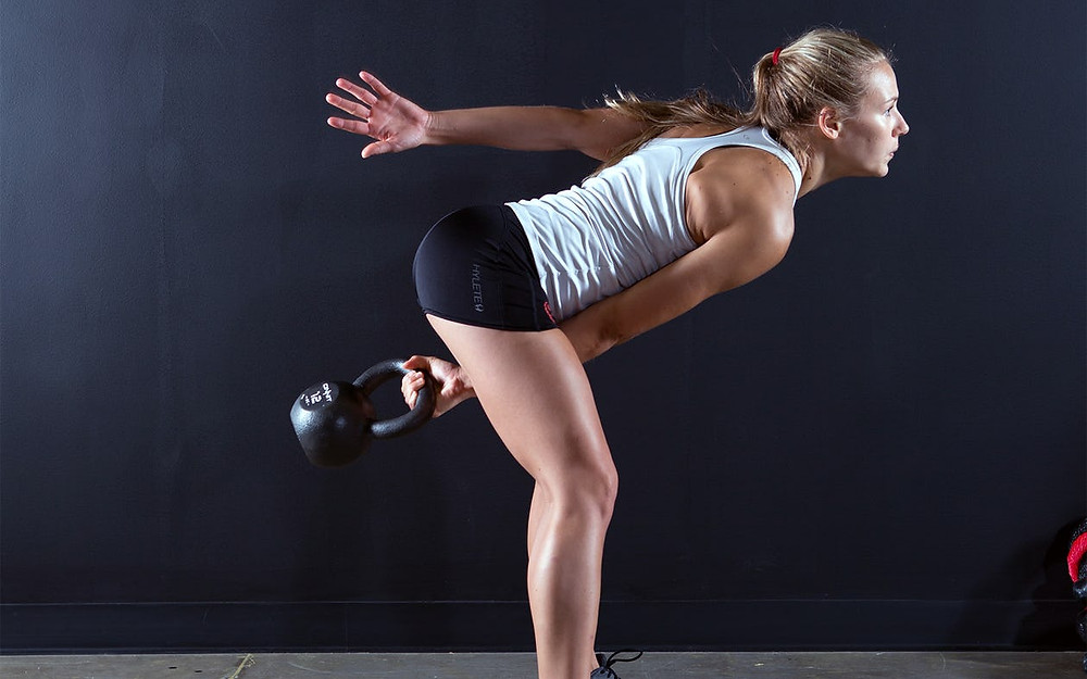 A woman performing a single hand kettlebell swing.