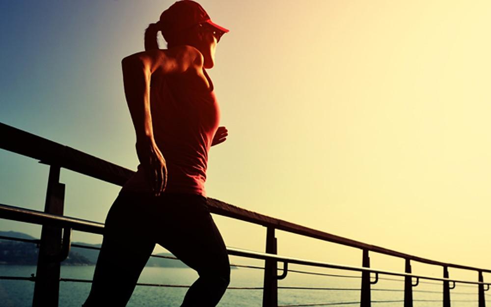a woman running across a bridge in the sun
