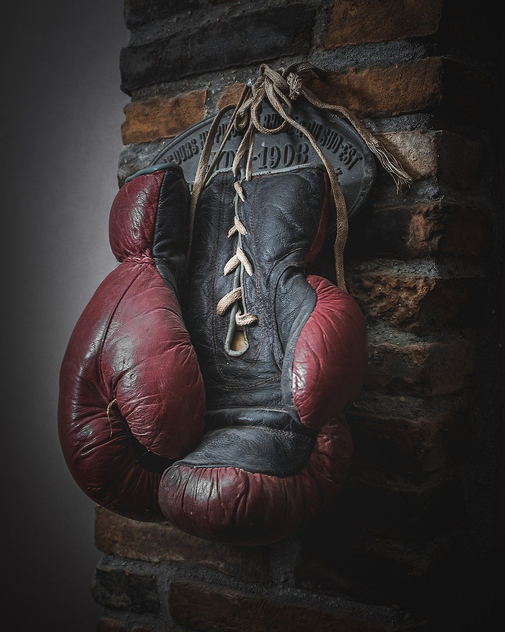 An old pair of 14oz boxing gloves hanging on wall.
