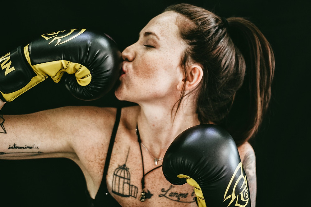 A female boxer is showing that she is happy with her 8 oz boxing gloves by giving one of the gloves a kiss.