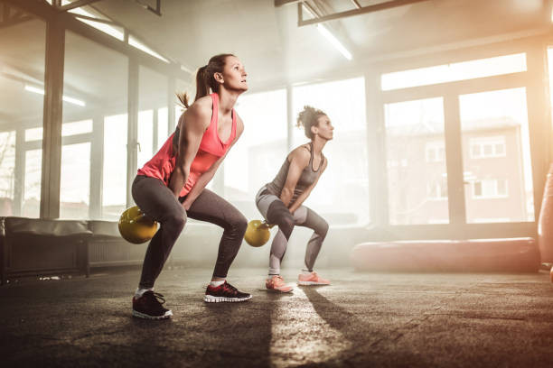Two woman performing the kettlebell swing. This is an excellent exercise for developing whole-body fitness. This article outlines the benefits of kettlebell swings.
