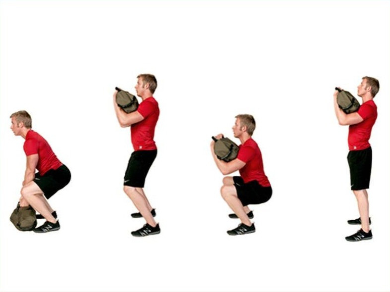 A man is performing sandbag exercises. He is performing the deadlift into hang clean to squat.