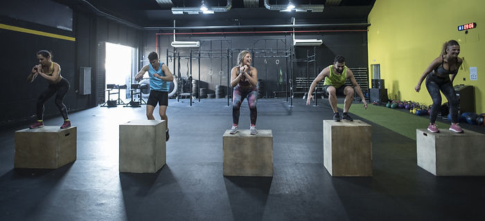 A group of fitness enthusiasts jumping on plyometric boxes. This image heads the Hungry4Fitness workouts blog page. s