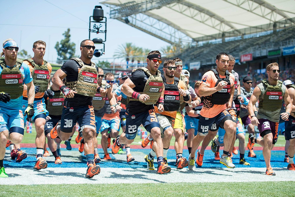 A group of CrossFit athletes wearing weighted vests 20kg are competing in an event. They are all wearing weighted vests while running.