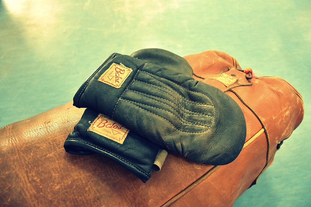 An old pair of 12 oz boxing gloves which have been placed on an old punching bag.