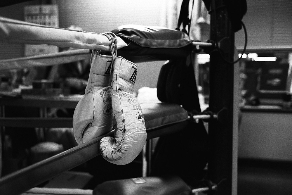 An image of a pair of the best boxing mitts. The boxing mitts are hanging over a boxing ring in a boxing gym.