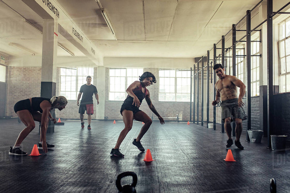 A group of people taking part in a kettlebell cardio workout as part of a health and fitness regime. They are working through shuttle sprints followed by kettlebell swings. They are exercising in a CrossFit style gym.