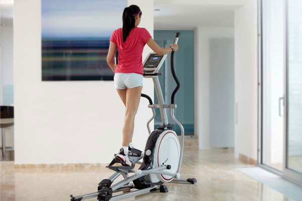 a woman on a cross trainer in her home gym
