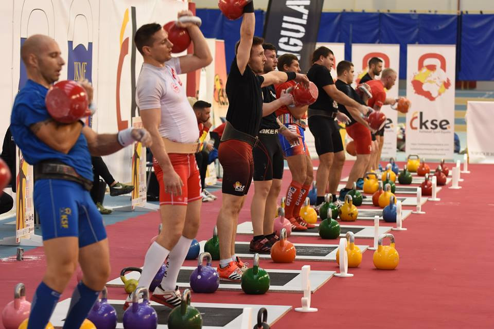 a number of men competing in a kettlebell competition