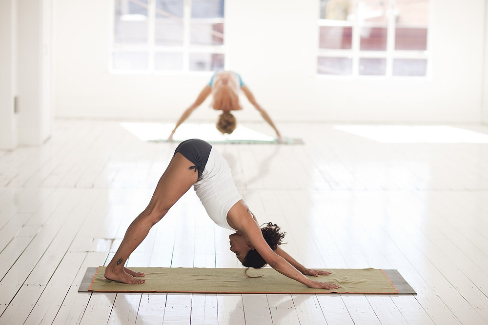 a woman on a yoga mat performing the downward dog movement